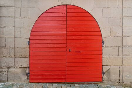 Red, freshly painted round wooden gate in an old facade of stone
