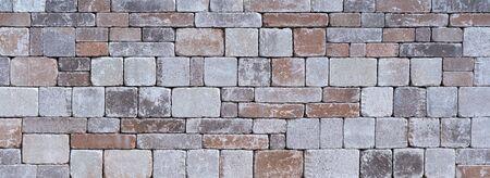 Steinmauer aus verschiedenen quadratischen Natursteinen Standard-Bild