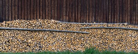 Panorama - Large pile of wood in front of a wooden barn wall