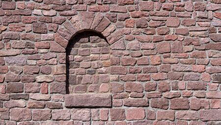 Reddish old wall with walled-up window