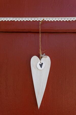 White wooden heart hangs on a red wooden wall