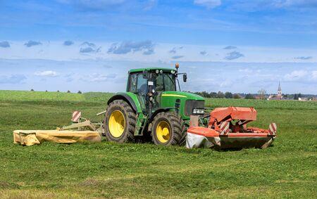 Traktor mäht Gras auf einem Feld Traktor mäht Gras auf einem Feld Standard-Bild