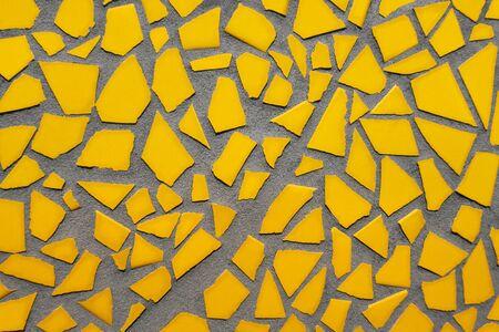 Mosaic of single yellow tile pieces on concrete Stockfoto