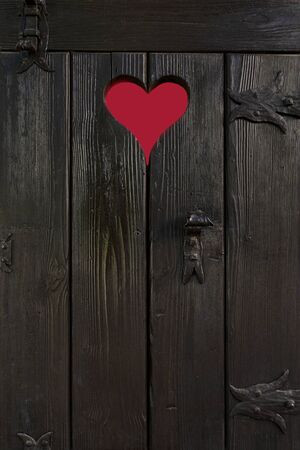 Old wooden little door with cut out heart