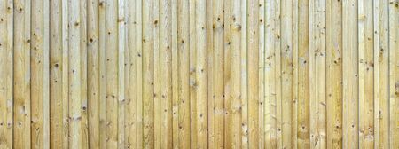Panorama of a untreated, slightly weathered, brown wooden wall with attached slats