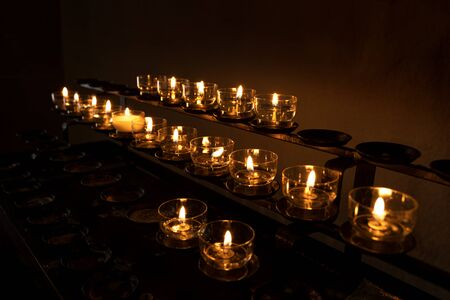 Small glass bowls with burning votive candles