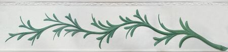 Relief of a green plant on a white wall with stucco ornaments