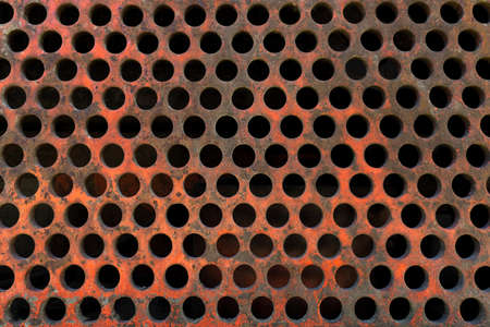 Very old, rusty, reddish perforated plate Stock Photo
