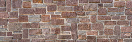 Panorama of an old wall made of red and gray sandstones with wide joints of gray mortar