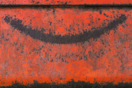 Old weathered red metal with a pattern in the shape of a laughing mouth in closeup
