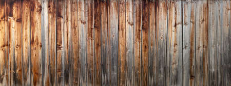 Panoramic detail of an old, weathered, gray brown wooden wall made of vertical boards