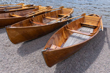 Rowing boats made of wood lie side by side in the fine gravel on the shore of a lake Stock Photo