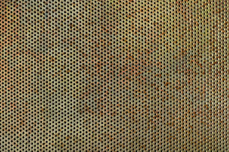 Old, rusted and weathered bright perforated plate in closeup