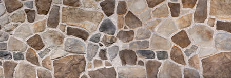 Wall made of brown and gray natural stones in different color shades and shapes Stock Photo
