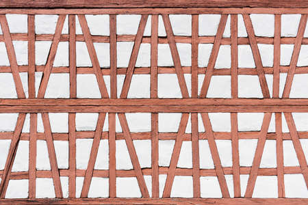 Detail of a half-timbered facade of an old model building house in reddish light brown with white Stock Photo