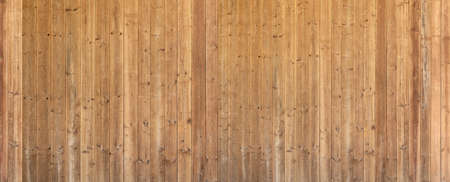 Panoramic detail of an old brown wooden wall made of untreated vertical boards