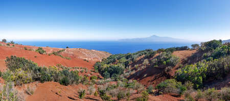 La Gomera - landscape of red earth with small bushes in the north above of Agulo with a view to Tenerife Stock Photo