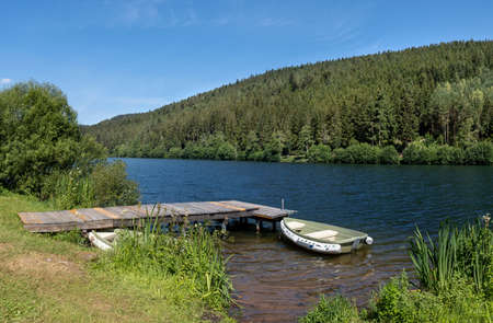 Wooden jetty with boat on a lake, taken at the dam Nagoldtalsperre in the Black Forest, Germany