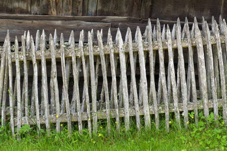 Old, heavily weathered gray wooden fences lean against the wooden wall of an old barn