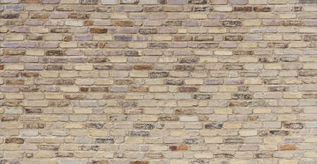 Old, beige brown, very roughly crafted brick wall, mostly painted over with light paint Standard-Bild