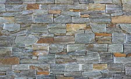 Detail of an exterior wall cladding made of facing bricks in stone look in gray with brown