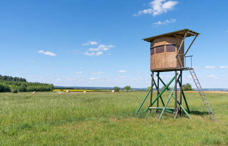 Closed deer stand on a meadow in wide rural landscape in sunny summer