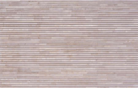 New modern bright wood cladding made of horizontal battens on a facade