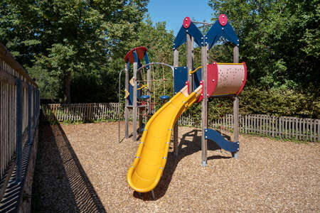 Colorful climbing frame with yellow slide on a small fenced playground with wood chips fall protection Foto de archivo
