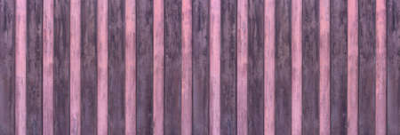 Old panoramic wooden wall made of vertical boards alternately painted in purple and pink