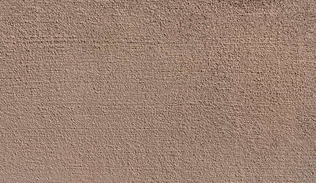 Close-up of new brown granular plaster on a sunny wall
