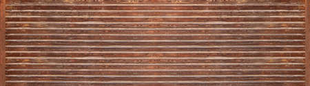 Brown horizontal panoramic wooden wall with intense grain, screws and applied, brightly weathered wooden strips Foto de archivo