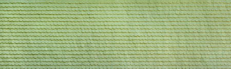 Panoramic facade made of light green painted wooden shingles in close-up
