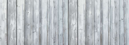 Light gray, partly weathered wooden wall made of vertical boards in panoramic close-up