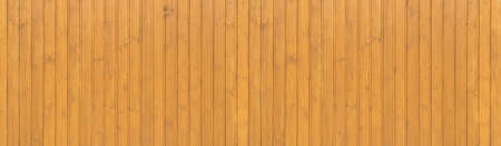 Honey-colored, yellow brown glazed wooden wall made of vertical boards in panoramic close-up Foto de archivo