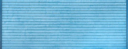 Detail of a wide, old, light blue garage door made of horizontal boards in a frame