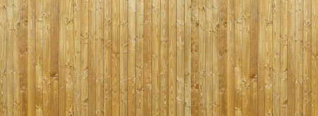 New wooden wall made of light brown, grained, vertical boards with two rows of small screws