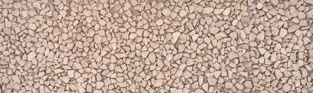 Panoramic close-up of exposed aggregate concrete made of small angular stones on a facade