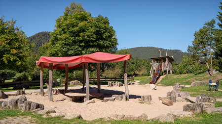 Playground in the park with textile roofing on wooden stakes in the sandy play area