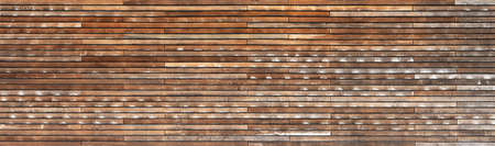 Weathered brown panoramic wooden wall made of horizontal battens in different shades Foto de archivo