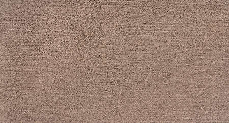 New granular brown plaster in close-up on a sunny wall Foto de archivo