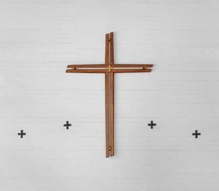 Large cross made of brown wood and four small metal crosses on a white wall made of exposed concrete