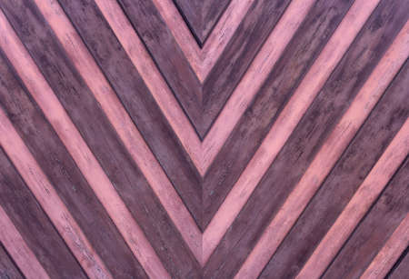 Detail of an old weathered wooden wall with pointed striped pattern in pink and purple