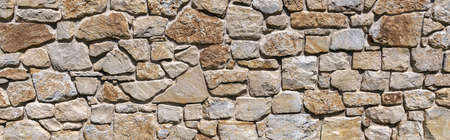 Brown gray panoramic natural stone wall with deep joints in the sunshine Foto de archivo