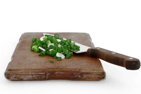 serrate: Serrate stone leek with knife on wooden cutting board