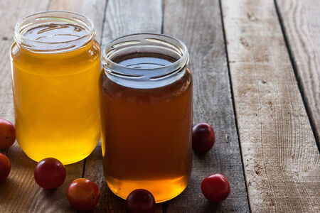 Two jars of different honey with plums on a old wooden table photo