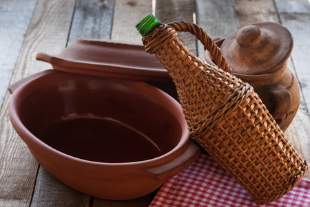 Old crocks with rattan bottle on old table photo