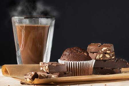 steamy: Hot steamy chocolate, stack of dark chocolate, chocolate muffin. Dark background, copy space.