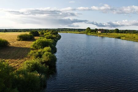 River in rural area with house on the bank under clody sky photo