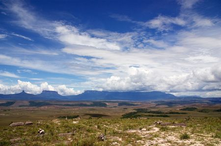 colorful cloudscape: Flat-topped mountains called Tepui in Gran Sabana, Guayana Highlands, Venezuela, South America, under blue sky with white clouds. Events of novel of A.Conan-Doyle The Lost World took place here Stock Photo