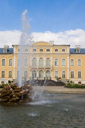 Fountain in foreground of entrance in yellow baroque\ palace